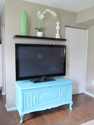 a bright aqua cedar chest with legs used as a tv console in a modern living room