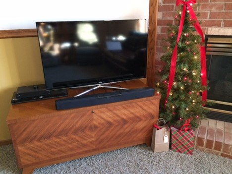 a wooden cedar chest creatively used as a tv console in a christmas decorated living room