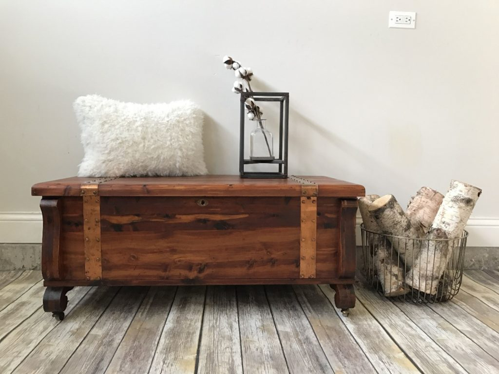 stylish cedar chest used creatively in a living room with a pillow and decor on its lid