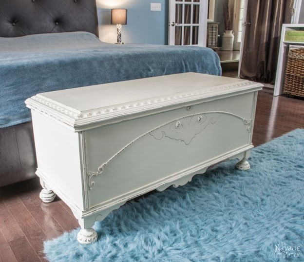 white refurbished cedar chest sitting at the end of the bed in a blue accented room