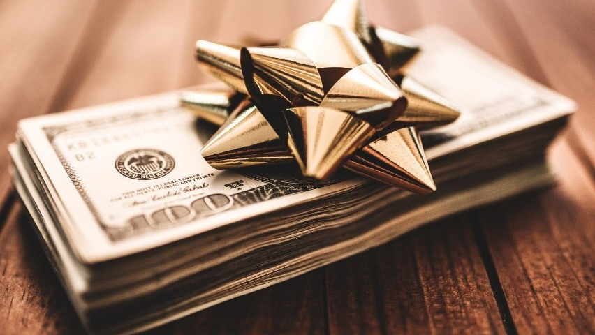 a pile of money with a bow as an expensive wedding gift downpayment for a house