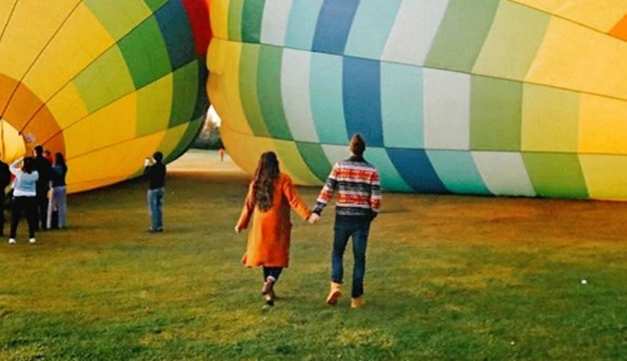 married couple holding hands walking to expensive wedding gift of a hot air balloon ride